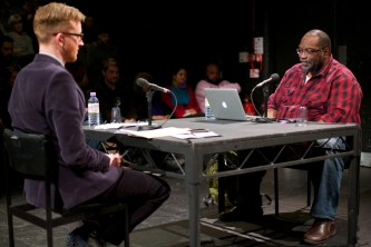 Fred Moten and Barry Esson sit across a table from each other in discussion