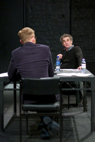 Howard Slater is in conversation at a table with Barry Esson in a black room