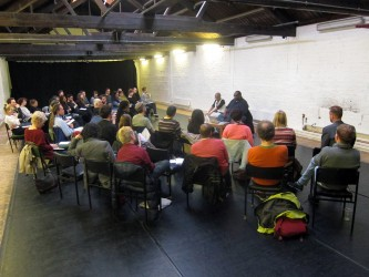 Long shot of the audience gathered around to take part in the discussion