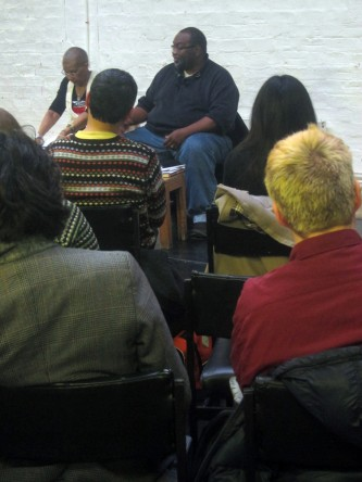 Fred Moten speaks, the shot is taken through two rows of audience members