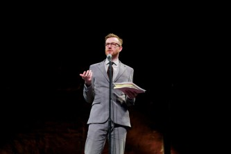 Barry Esson Introduces the performance he holds a notebook and wears a suit