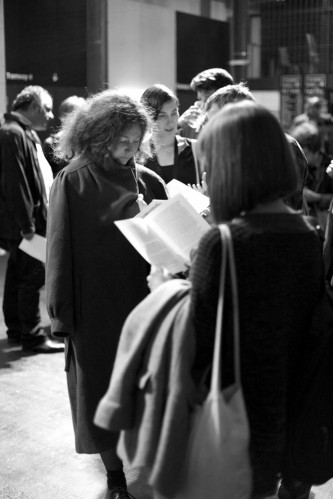 Audience members read the handout after the performance in a foyer