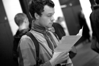 An audience member reads a handout in the foyer