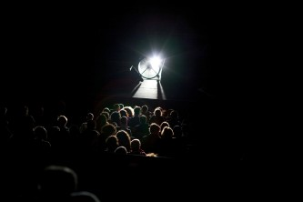 The audience is illuminated by a strong light and hit with wind from the fan