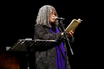 Sonia Sanchez holds a book she reads poetry from it. She wears a purple scarf
