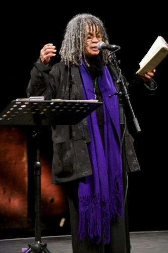 Sonia Sanchez gesticulates as she reads poetry. She wears a purple scarf