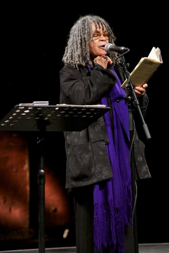 Sonia Sanchez clenches her hand to her face with closed eyes as she reads poetry