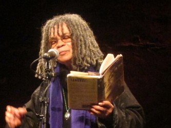 Sonia Sanchez has her closed eyes as she reads poetry whilst holding a book