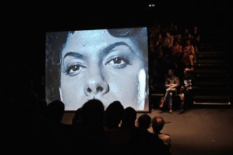 A film plays on a screen, on which there is a B&W close up of a woman's face
