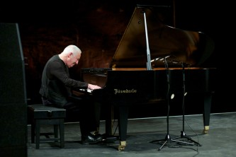 John Tilbury plays a grand piano in a dark theatre space