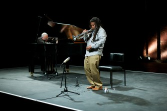 John Tilbury plays a piano whilst Wadada Leo Smith plays a trumpet
