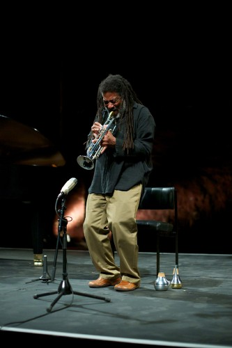 Wadada Leo Smith bends his knees as he plays trumpet