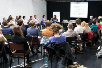 A long shot of the audience taking part in a discussion in a naturally lit room