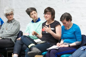 A shot of four audience members, one of whom is asking a question