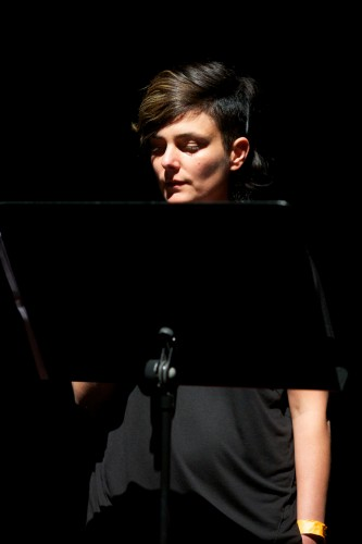 Pauline Boudry presents and talks in a dark room, their face dramatically lit