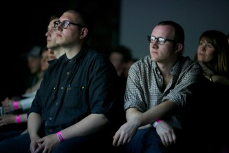 Audience members faces are illuminated by the film they are watching