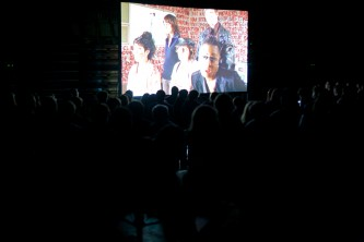 Silhouettes of audience members as they watch a film