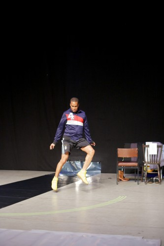 Trajal Harell dances in a sports top and shorts in a theatre space
