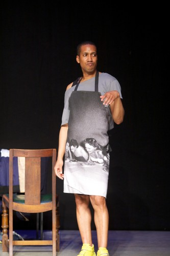 Trajal Harell poses, one wrist cocked, in a apron