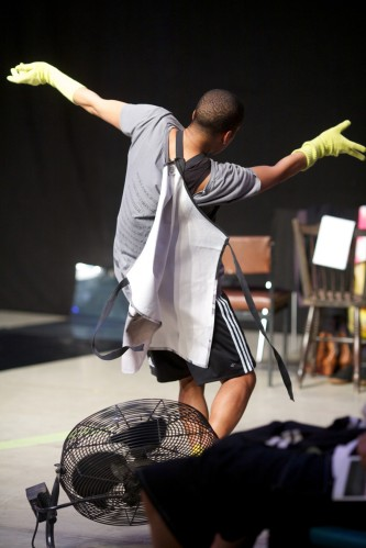 Trajal as his arms are wide, whilst wearing an apron and washing gloves