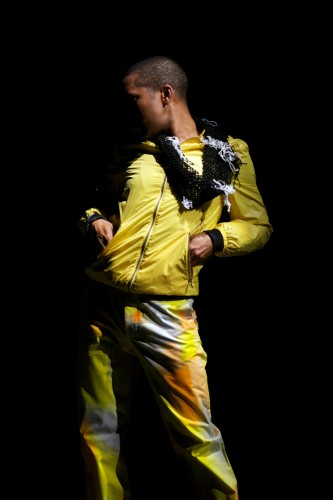 Trajal Harrell poses wearing yellow tracksuit, hands in pockets
