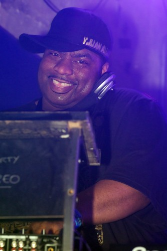 Vjuan gives the camera a cheeky grin whilst DJing