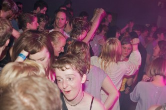 A shot of a packed dance floor bathed in pink light, lots of smiles