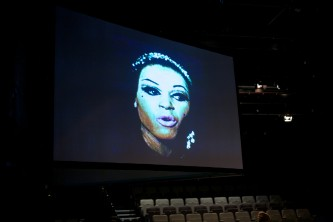A screen shows a feminine face, glamorously made up, singing
