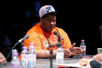 Vjuan Allure, in an orange t-shirt, talks into a mic during the discussions