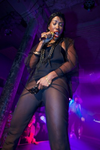 Miss Prissy sings into a gold mic in bet jumpsuit