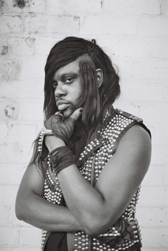 M Lamar places hand on chin as they pose for a portrait