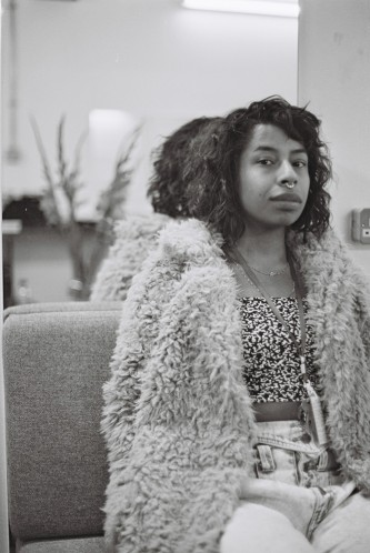 Kia Labeija in a furry jacket sits on a sofa posing for a portrait