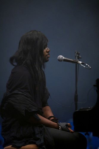 A profile shot of M Lamar by a piano as they prepare to perform