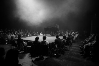 M Lamar on piano on a central stage surrounded by seated audience