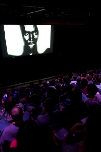 The audience sit in rows watching a Grace Jones video