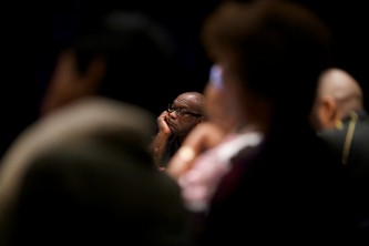 Fred Moten listens, hand cradling his chin, audience members in the foreground