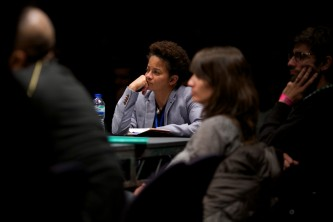 Kara Keeling listens hand on chin, audience members in the foreground