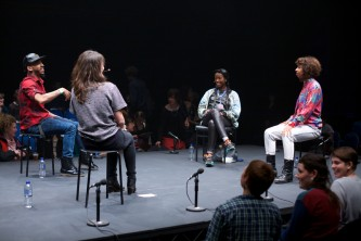 four people sit on a stage looking at each other and smiling