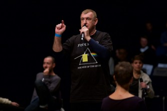 A member of Ueinzz in a pink floyd t shirt speaks into a microphone