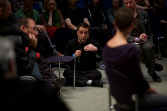 A member of Ueinzz sat on the floor speaks into a microphone
