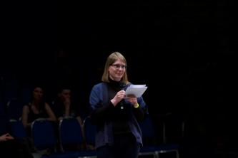 Bryony McIntyre smiles and holds a mic and paper in a dark space