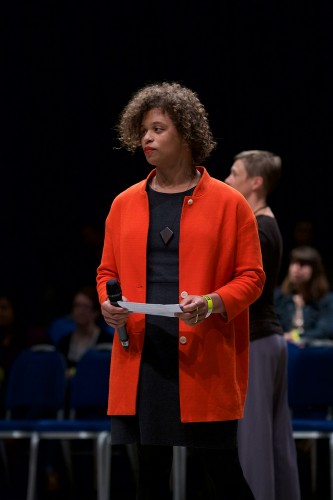 Reina Gossett in a red coat speaks holds a mic and a piece of paper