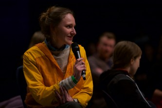 Park McCarthur in a yellow jacket asks a question to the group