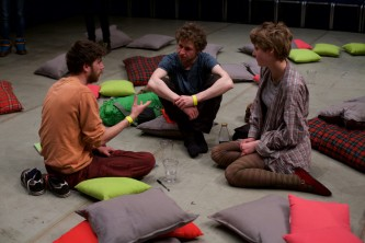 Audience members sit on cushions on a grey floor