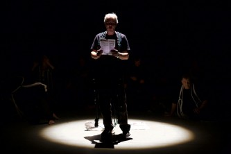 A member of Ueinzz reads aloud from a paper in a spotlight