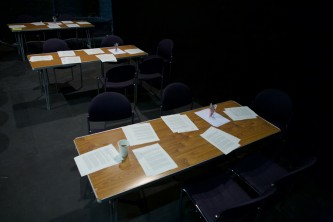 Tables set out with papers in a dark room in preparation for a workshop