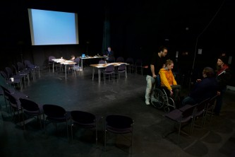 A dark room is set out with a screen and chairs in preparation for a workshop