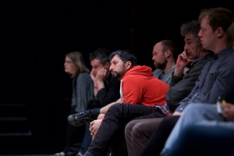 An audience member in a red top leans forward as they listen