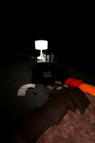 A dark room has coloured blankets and cushions and lamps arranged in it