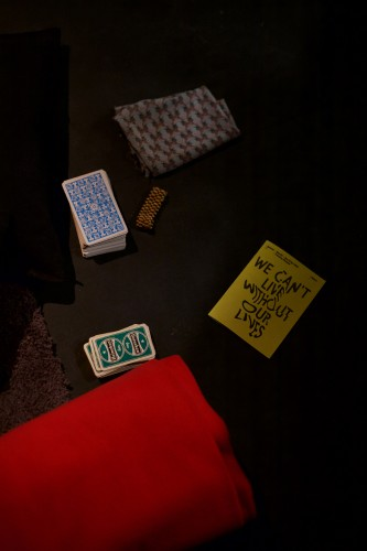 Several packs of cards are lain out on the floor next to a red blanket